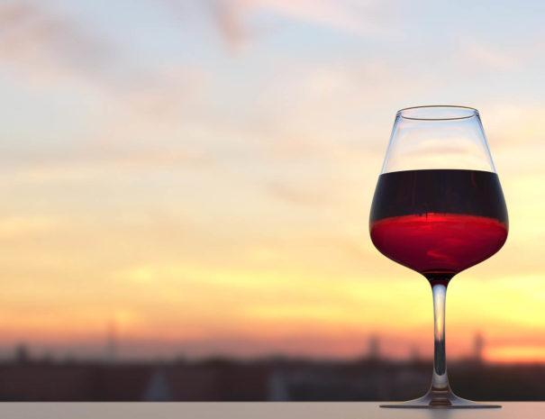 Copa de vino en una azotea con vistas a una puesta de sol en Barcelona
