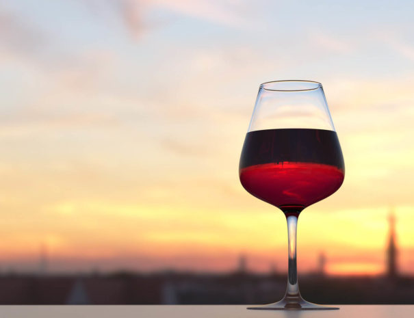 Glass of wine on a rooftop with a sunset view